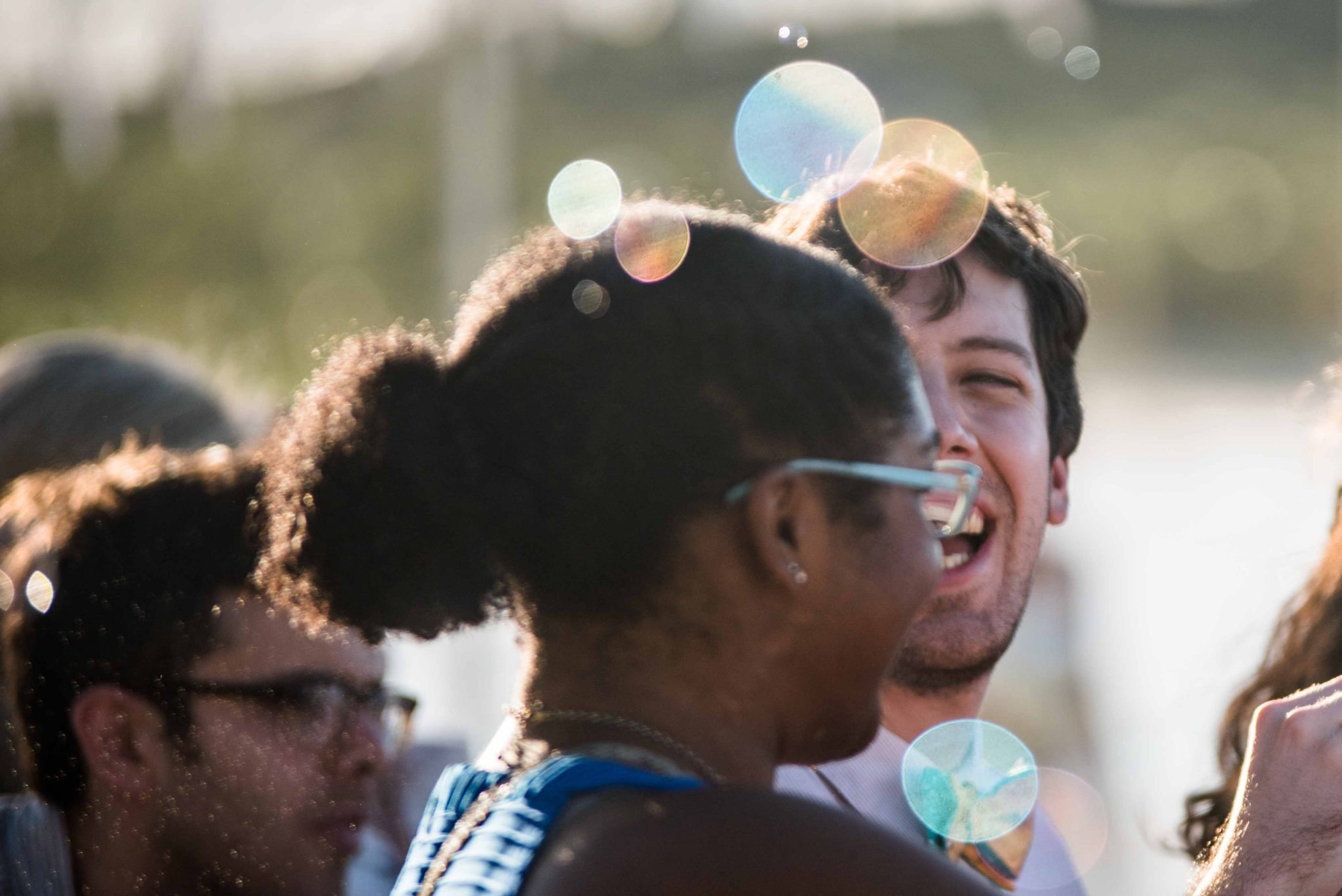 Guests laughing blowing bubbles for wedding photos