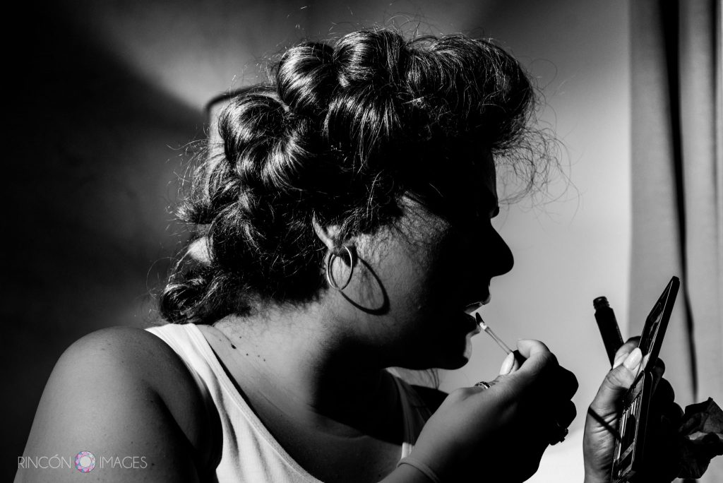 Silhouette photograph of the bride applying lipstick in a small hand mirror.