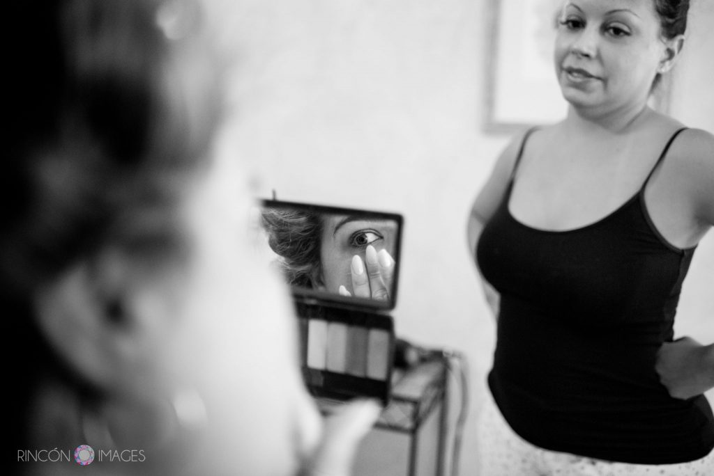 Black and white photograph of the bride doing her makeup in a small mirror while one of her bridesmaids looks on.