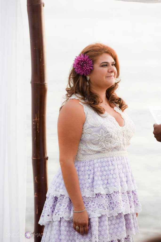 The bride standing in her purple and white beaded wedding dress with a purple flower in her hair in front of the ocean.