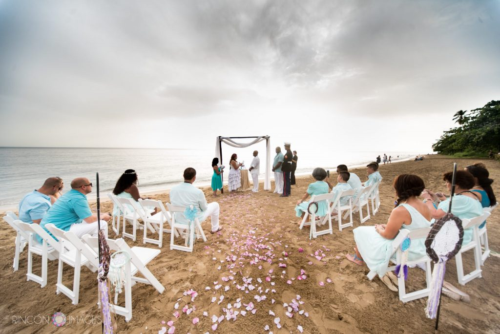 Photograph that shows the entire beach wedding ceremony set up with guests siting in white chairs and the bride and groom standing at the bamboo altar on the beach in Rincon, Puerto Rico.