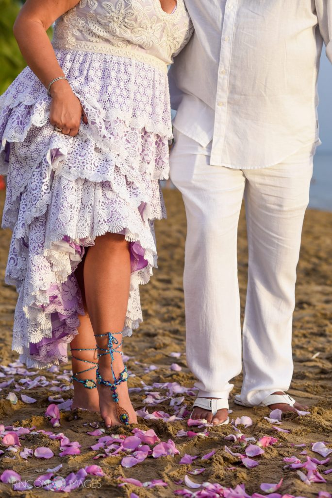 The brides feet standing next to the groom with pink rose petals on the sand.