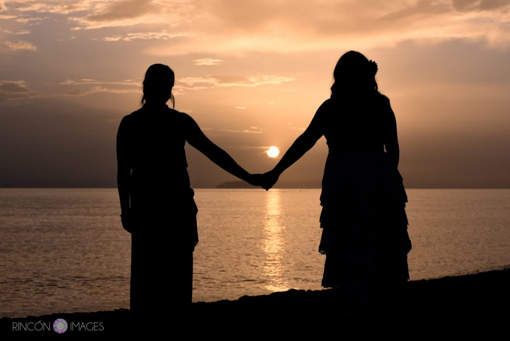 The bride and her bridesmaid holding hands as the sun is setting while they look out at the ocean.