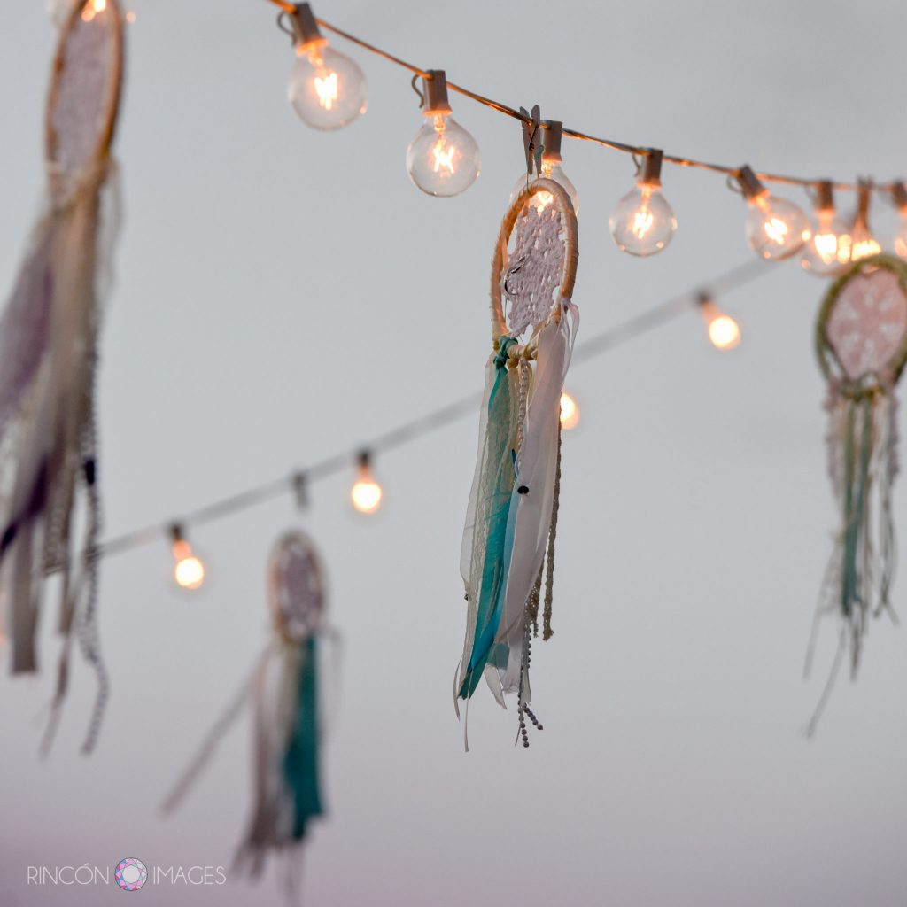 Hand made dreamcatcher wedding decorations hanging from outdoor string lights at sunset during the wedding reception.