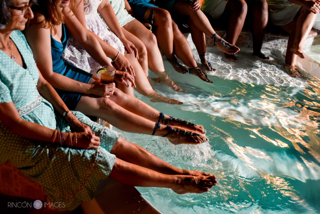 Wedding guests dip their feet in the pool during the wedding reception.