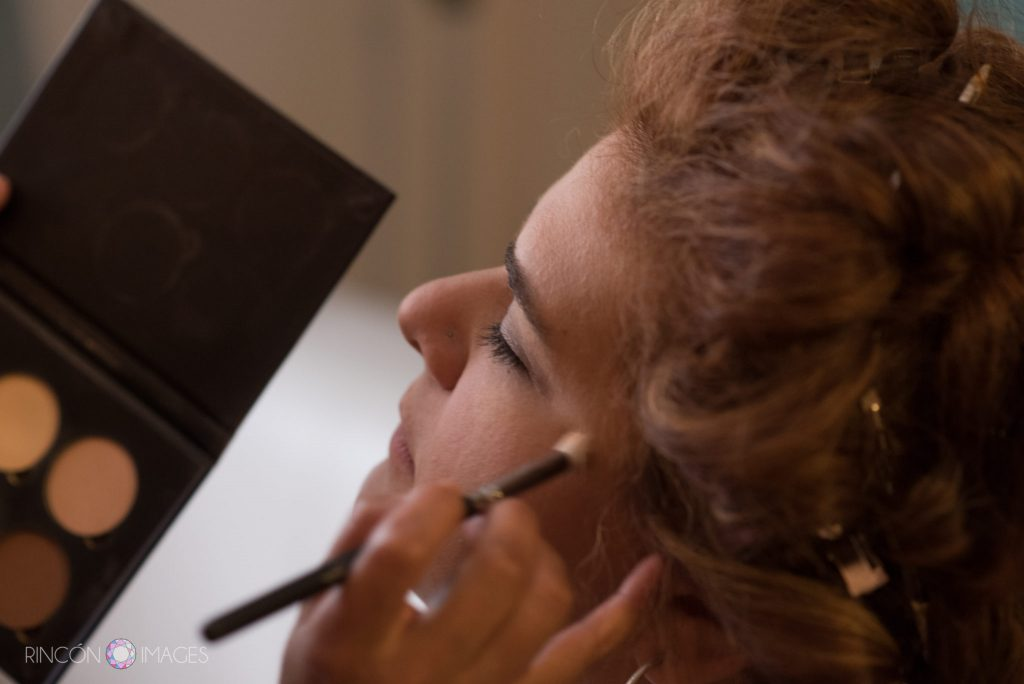 Close up photograph of the brides face as one of her bridesmaids applies make up.