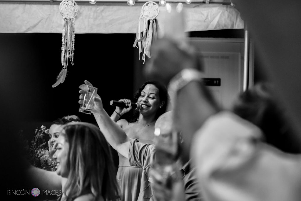 Black and white photograph of the maid of honor giving a toast on the microphone while guests hold up their glasses.