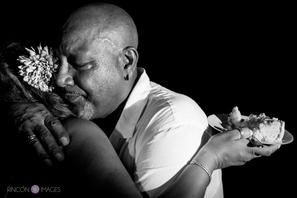 Black and white photograph of the groom hugging the bride after the cake cutting ceremony.