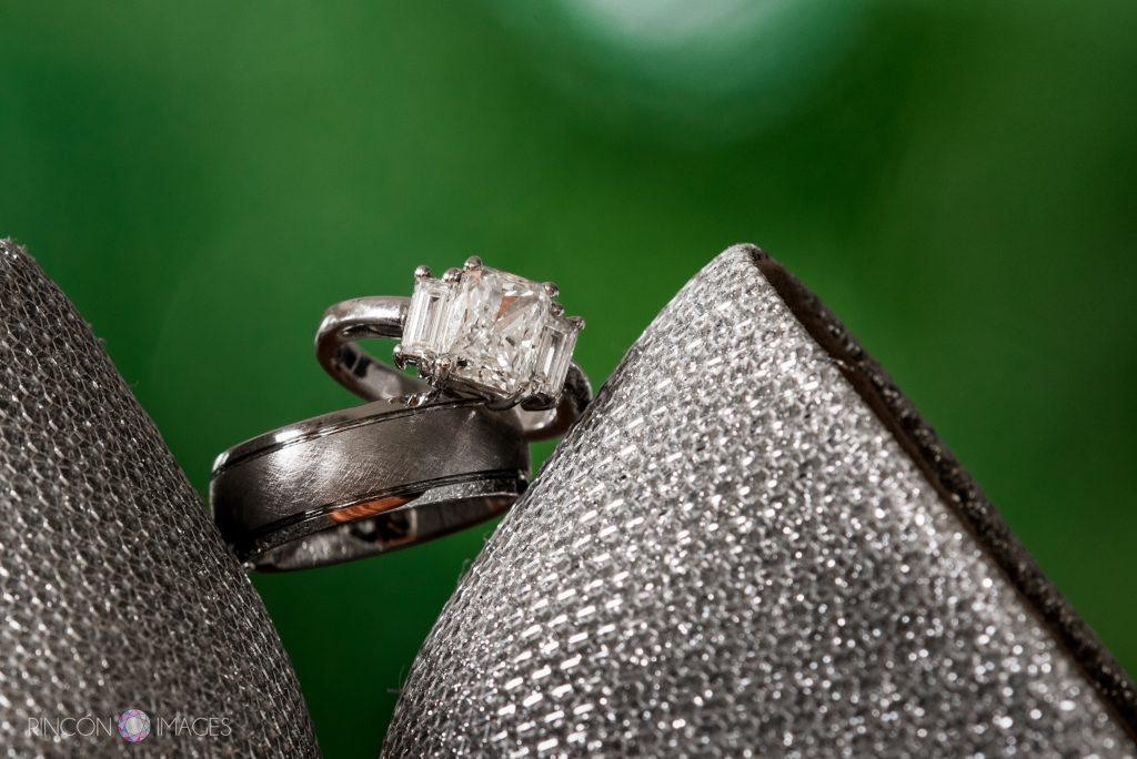 Diamond wedding ring and grooms wedding ring on a green background.