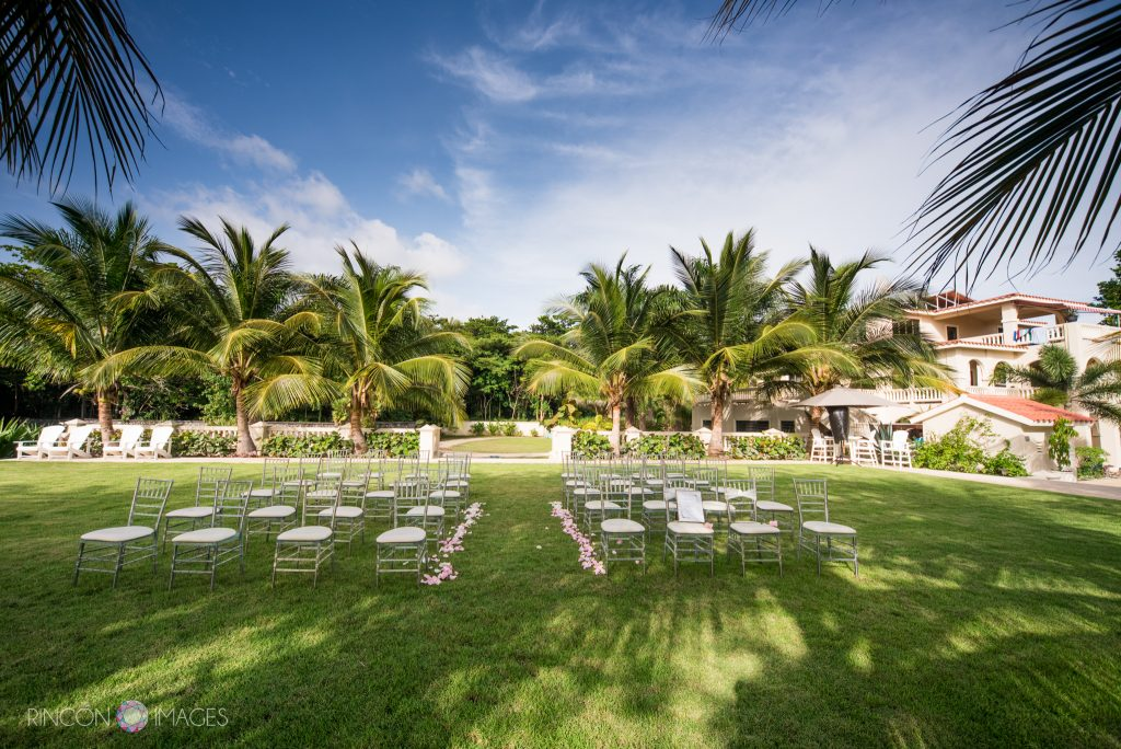 Wedding ceremony setup with twenty white chairs setup on a green lawn in a tropical backyard with palmtrees and a blue sky.