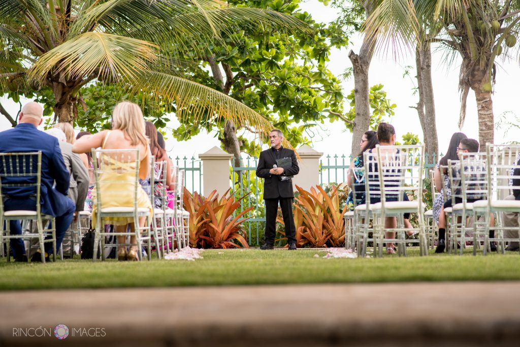 Photo of a minister standing in front of a group of people sitting before the start of a wedding ceremony on a lush green lawn with palm trees.
