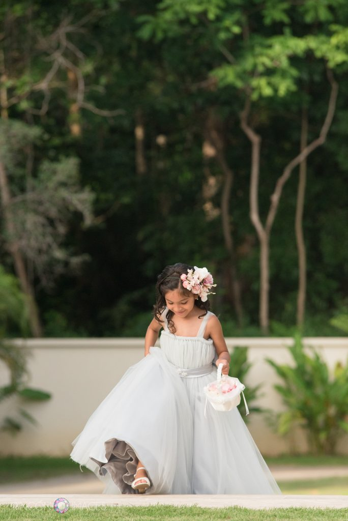 A flower girl wearing a grey dress takes a step up the staircase to start processing to the front of the wedding ceremony.