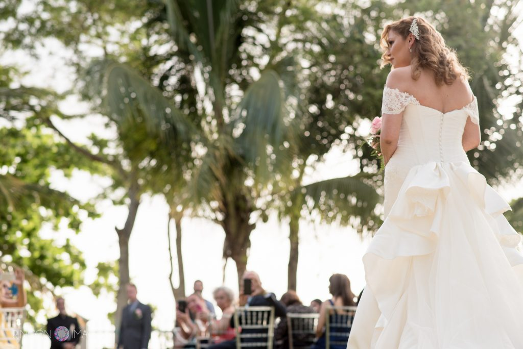 Bride in a white dress about to start walking down the aisle in front of lush green palm trees.