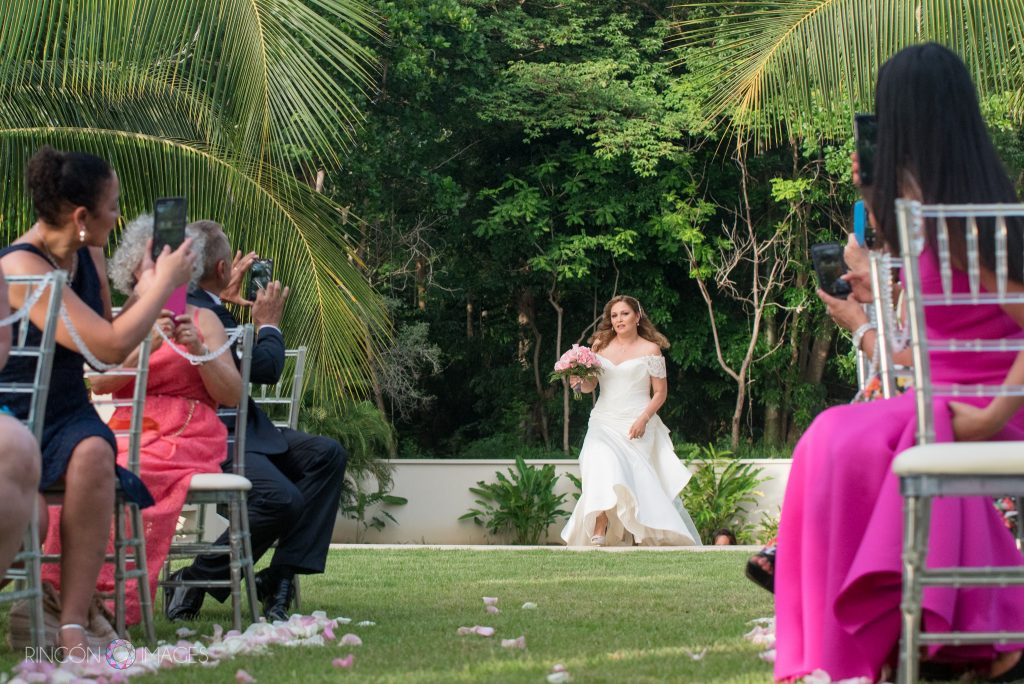 Photograph of the bride from the front starting to walk down the aisle in her white wedding dress. The bride is carrying a bouquet of pink roses the setting is a tropical backyard with green grass and palm trees.