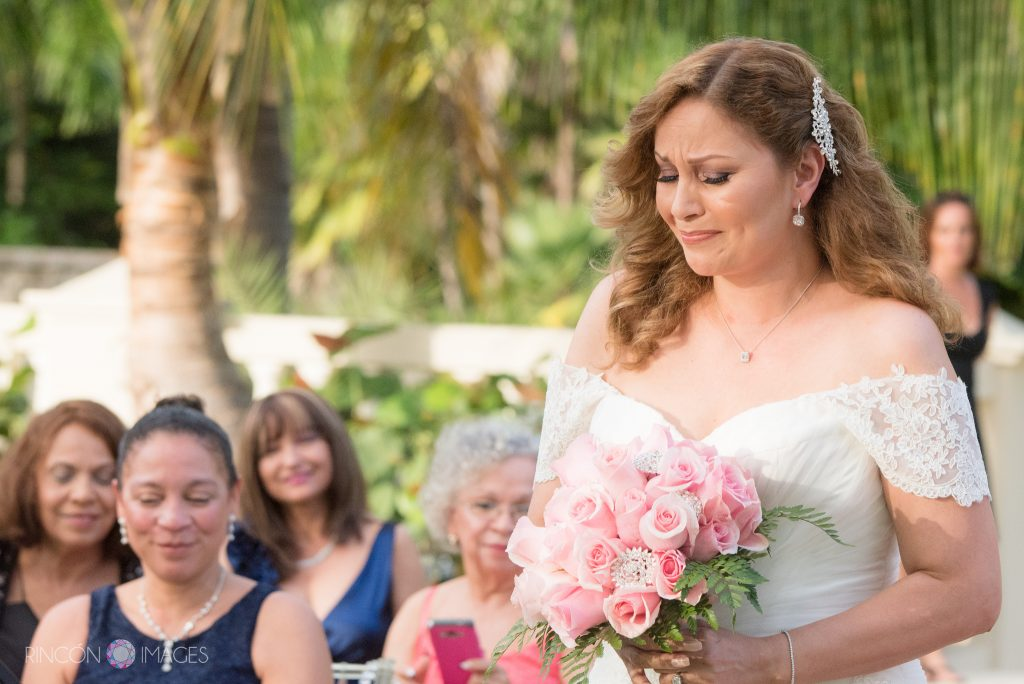Bride wearing a white dress holding a bouquet of pink roses starts to tear up as she walks down the aisle towards her groom.