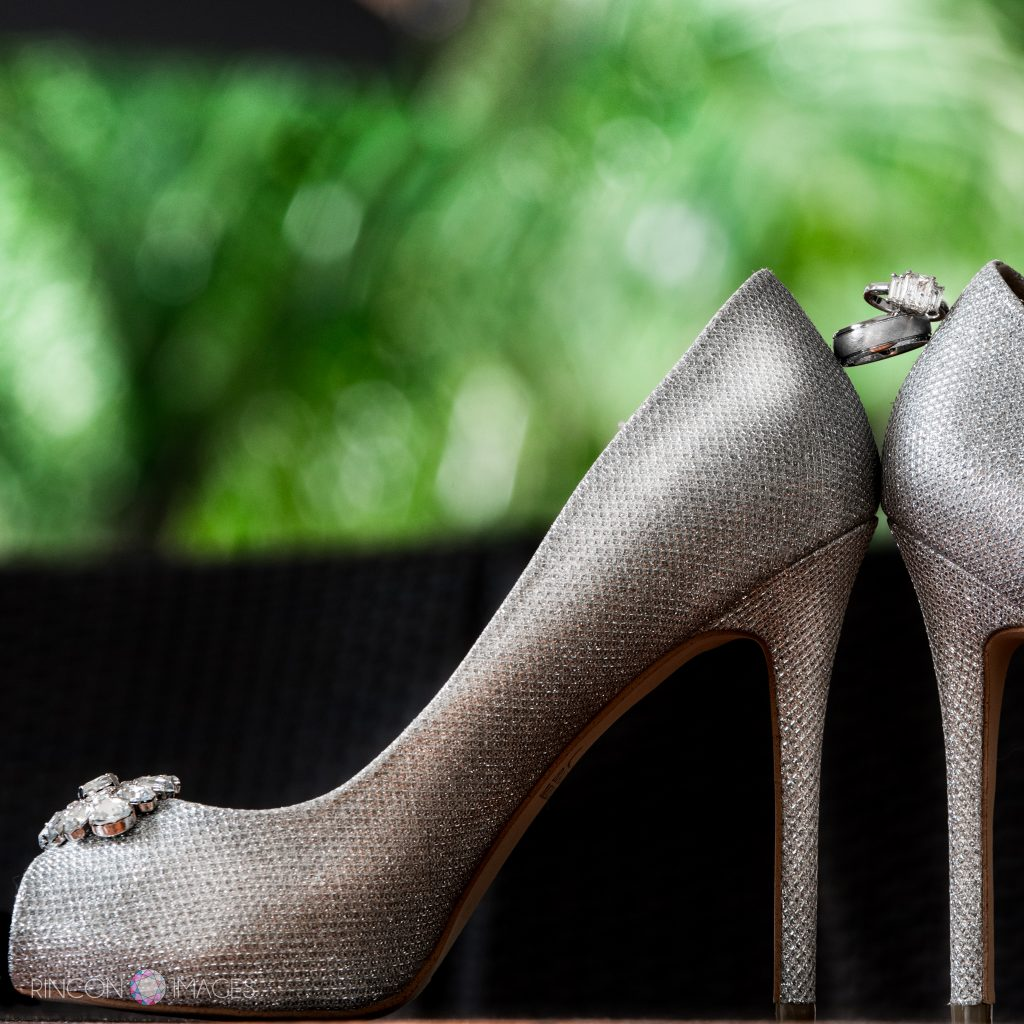 Diamond wedding rings balanced between two silver wedding shoes in front of a green background.
