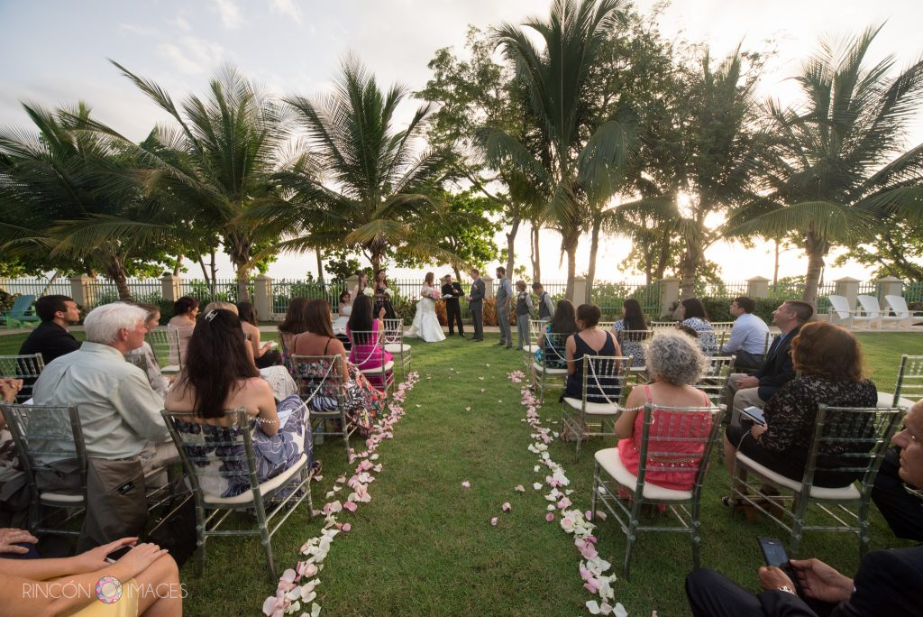 Photograph of the entire wedding ceremony site, there are pink rose petals going down the aisle and a row of palm trees behind the bride and groom. The ceremony is on a green grass lawn.