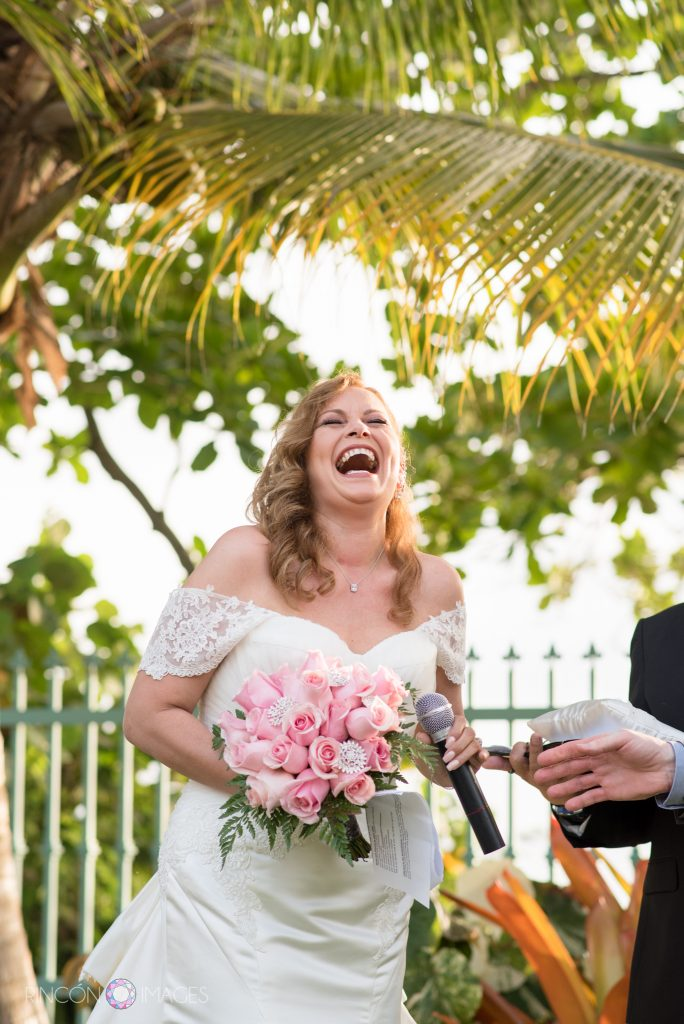 Bride wearing a white dress holding a bouquet of pink roses laughs and smiles while holding the microphone during her ceremony.