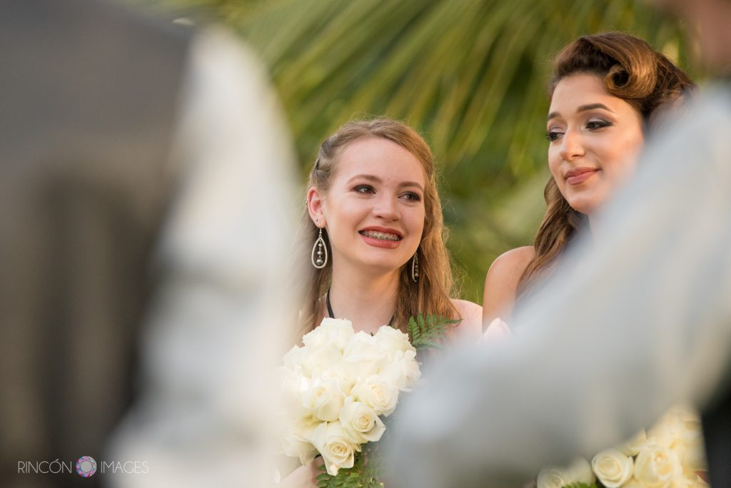 The two bridesmaids smile while holding bouquets of white roses.