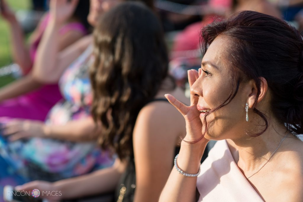 One of the guests sitting during the ceremony wearing a pink dress wipes a tear from her eye.
