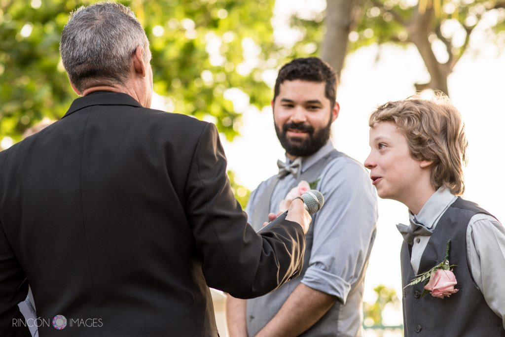 The young son of the groom speaking into the microphone during the wedding ceremony while his older brother looks on.