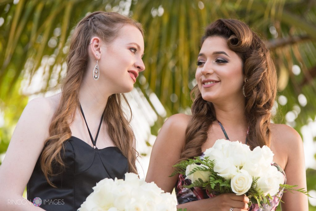 The two bridesmaids wearing black dresses and holding white rose bouquets smile at each other, the girl on the left has tears in her eyes.