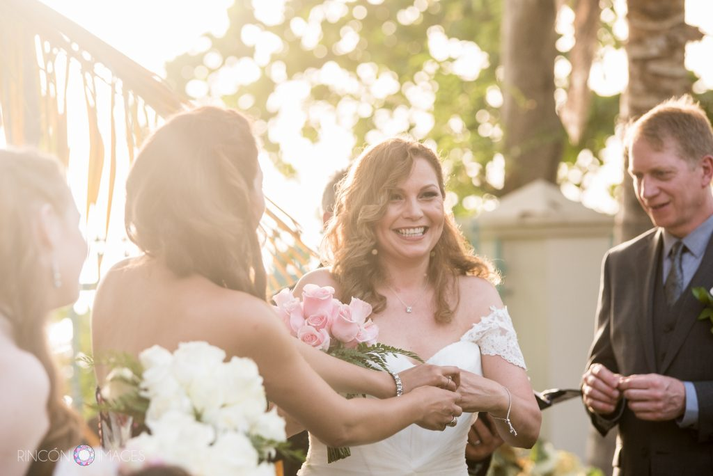 Funny sunlight filled photograph of the brides daughter trying to help her get her engagement ring off during the wedding ceremony before the exchange of the rings.