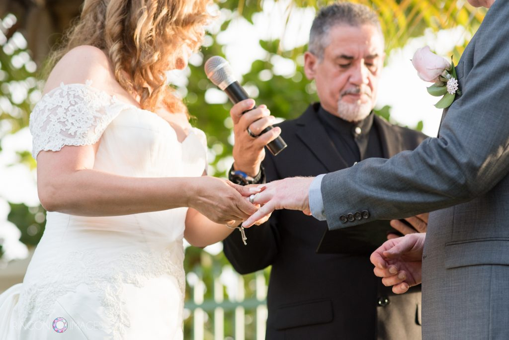 Photograph of the bride wearing a white dress speaking into the mircophone while putting the wedding ring on her grooms finger.