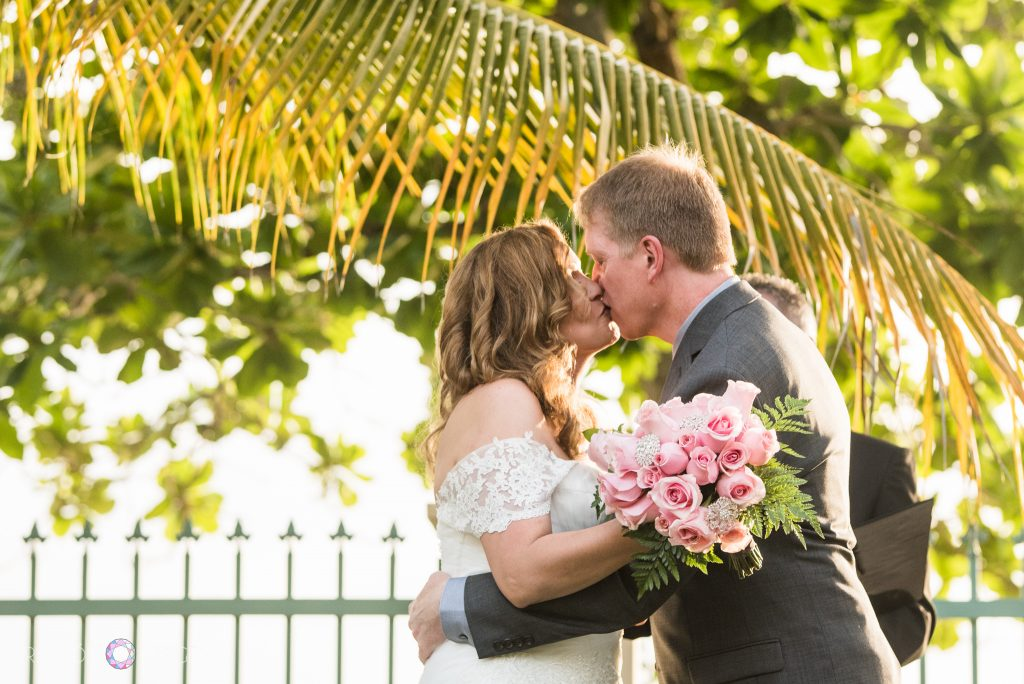 The bride and groom kiss in front of a green and yellow palm fraun background, the bride is holding a bouquet of pink roses and the groom is wearing a grey suit.