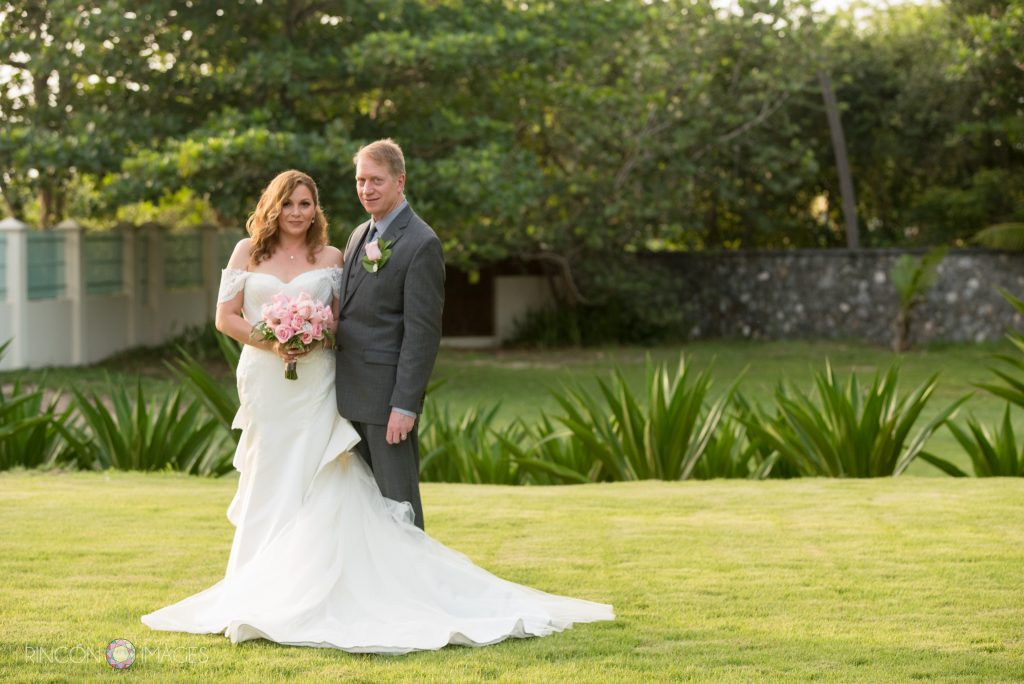 Formal wedding photograph of the bride wearing a white dress holding a bouquet of pink roses standing next to her groom wearing a grey suit on a beautiful green lawn with lush trees in the background.