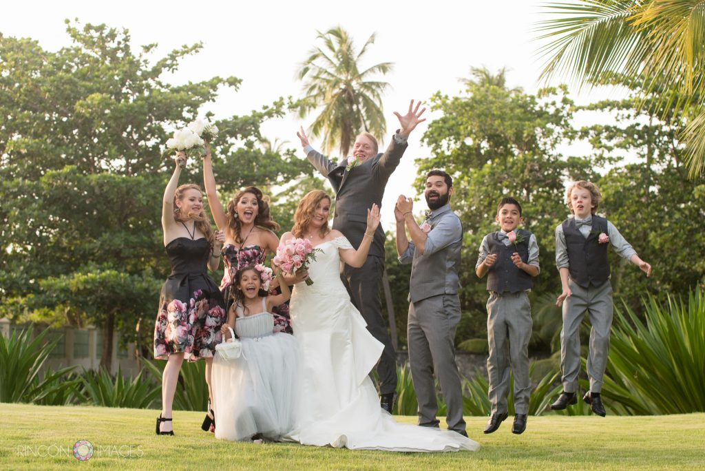 Fun photograph of the bride, groom, and their five children jumping with joy on a green grassy lawn in front of palm trees.