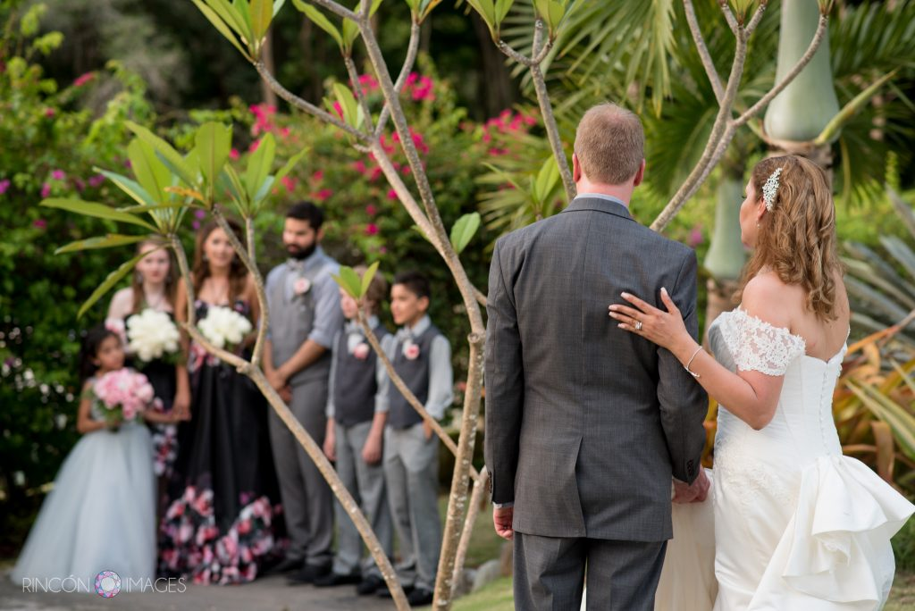 The bride and groom have their backs turned to the camera as they look on at their five children posing for a photograph being taken by another photographer in front of pink tropical flowers.
