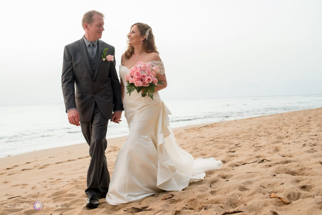 The bride wearing a white wedding dress carrying a pink rose bouquet walks with her groom wearing a grey suit toward the camera holding hands on the beach.