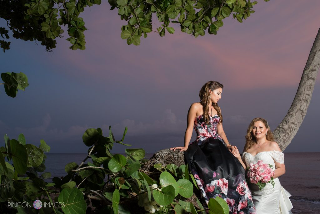 The bride standing with her daughter who is sitting on a tree branch. The daughter is wearing a black dress with pink flowers on it they are both standing in front of a beautiful blue and pink sunset.