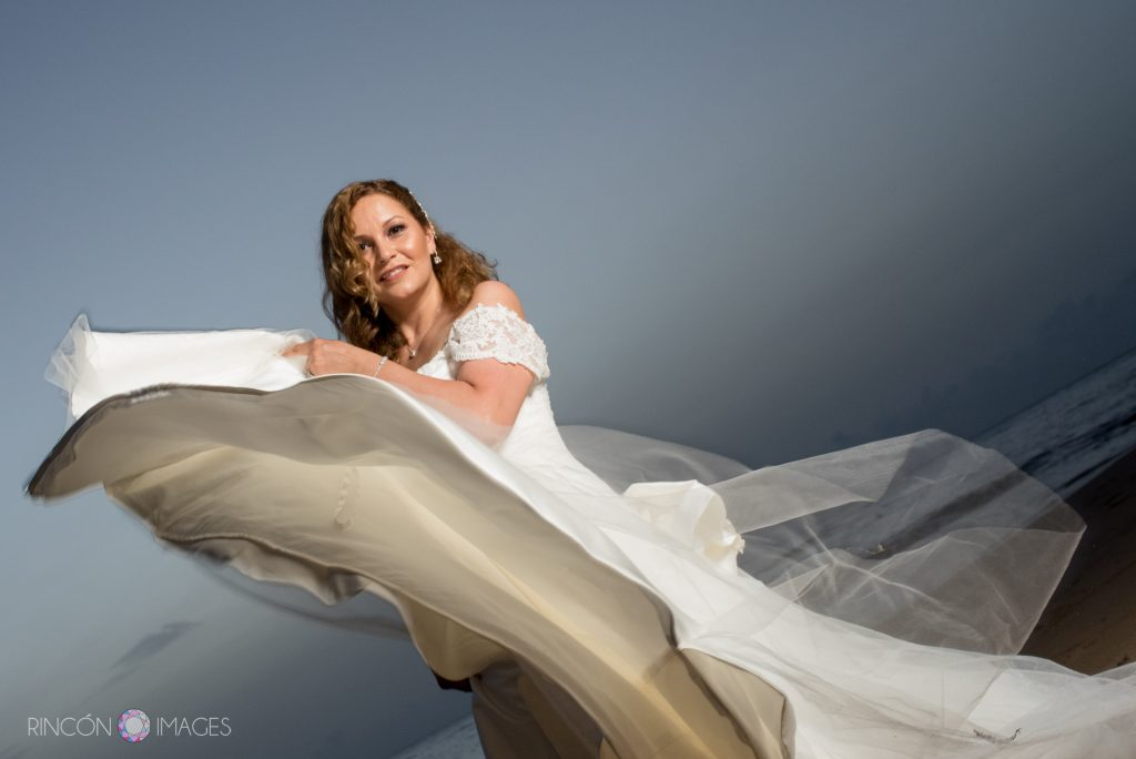 The bride swishes her long white dress in front of the camera as she spins on the beach.