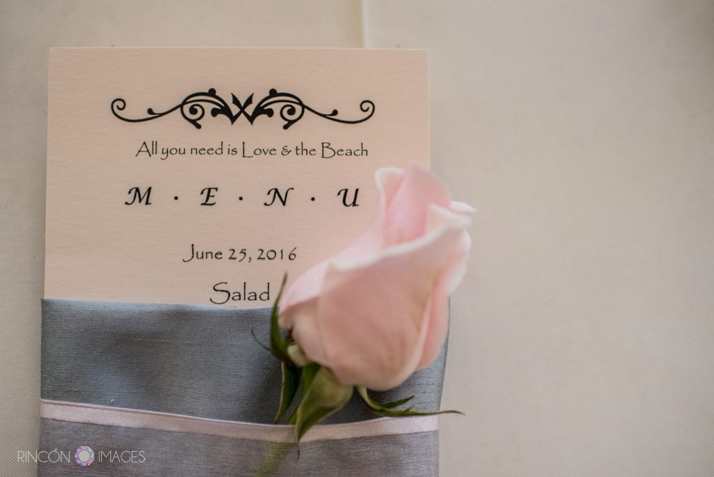 Photograph of the dinner menu for the wedding. There is a grey napkin with a pink ribbon and a pink rose along with the menu.