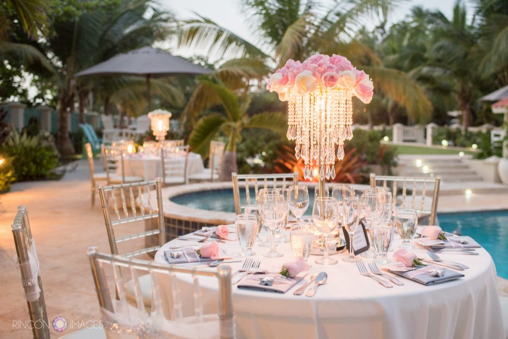 Photograph of the table setup during the wedding reception by the pool. The tables have white table clothes with large centerpieces that have pink roses and dangling strings of crystals. The tables are setup outside by the pool surrounded by palm trees.