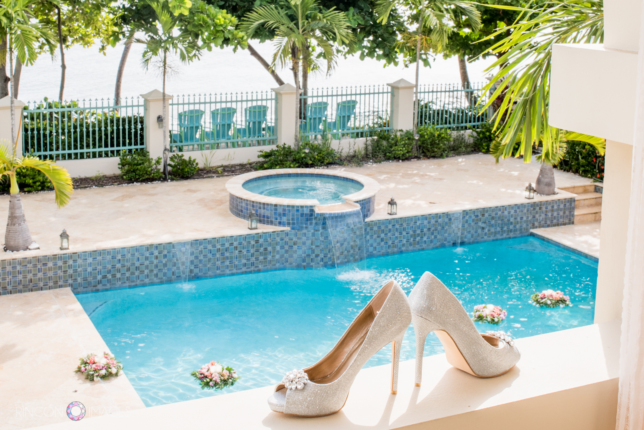 The brides silver wedding shoes on the balcony ledge with the swimming pool and palm trees in the background.