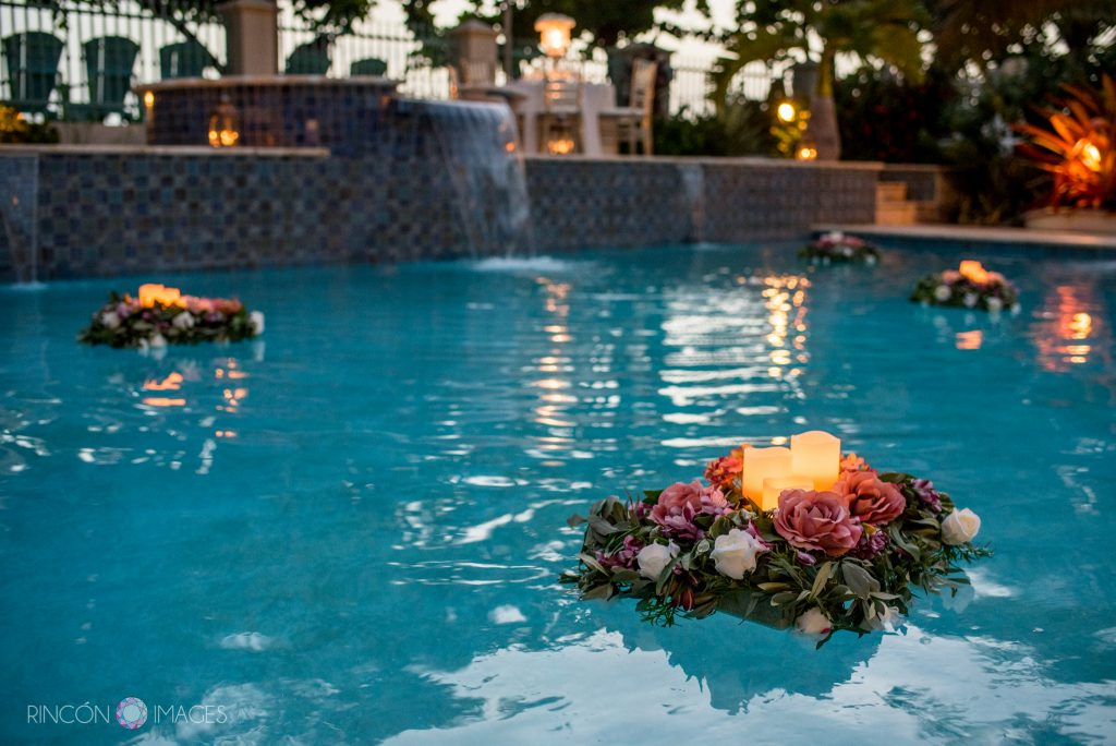 Flower arrangements with candles floating in the swimming pool.