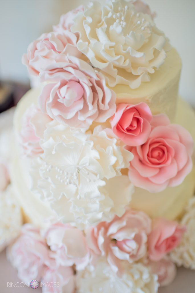 Photograph of a beautiful white wedding cake decorated with edible pink and white roses made of icing.