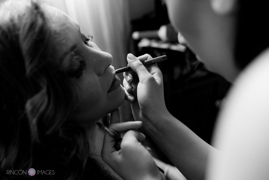 Black and white photograph of a brides face as her daughter applies lipstick for her before the wedding.