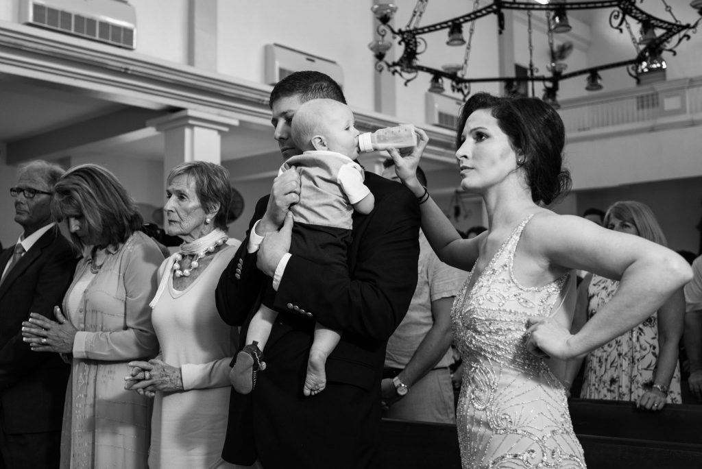 Mother feeding her baby during a wedding ceremony in Rincon, Puerto Rico.