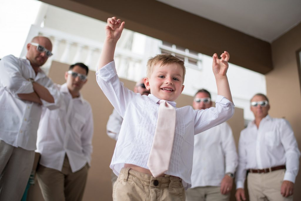Children at weddings looking cute in a pink tie and white shirt in front of a line of groomsmen.