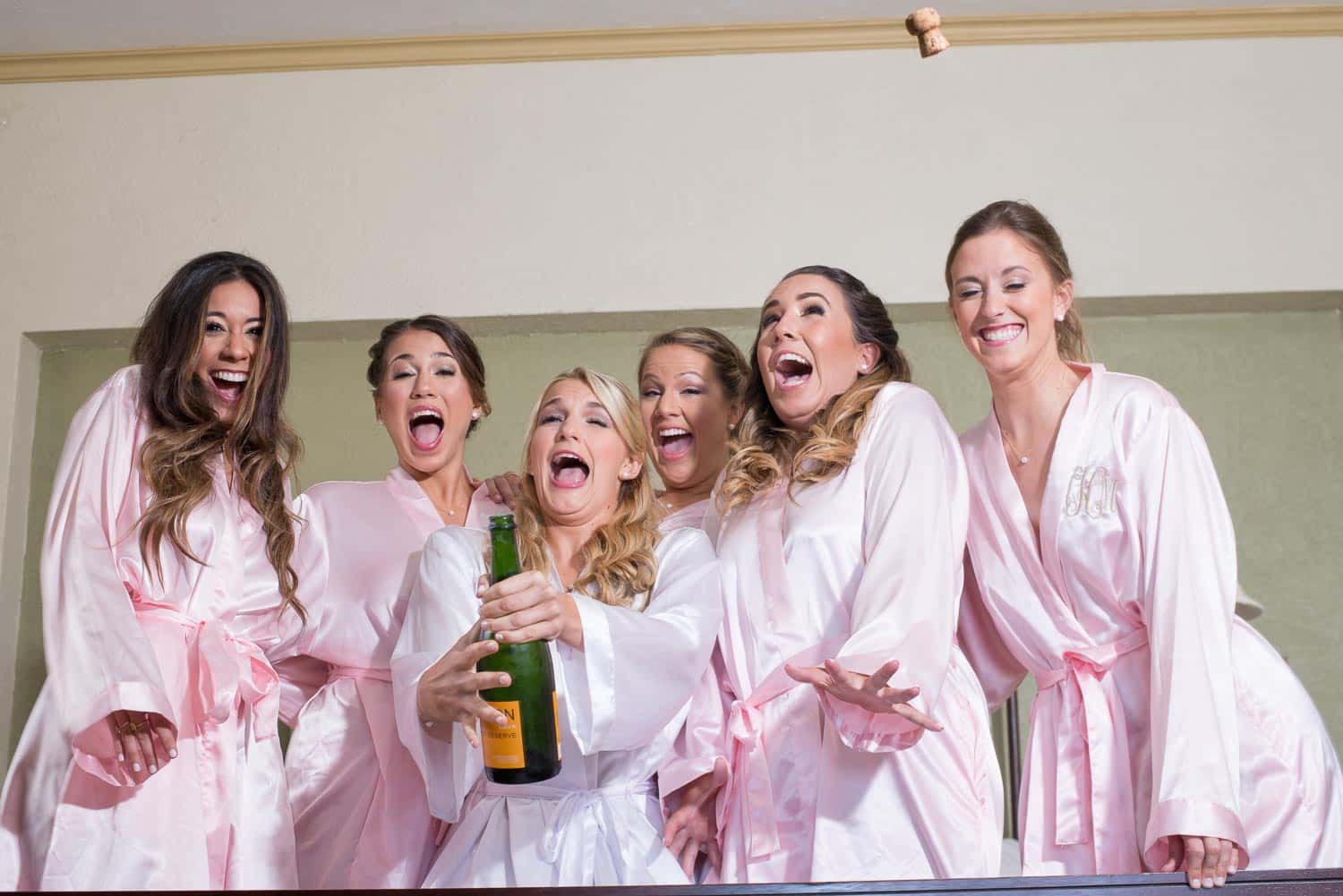 Bride and bridesmaids laughing while opening champagne