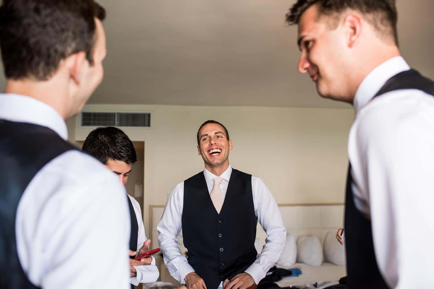 Groomsman laughing in their hotel room