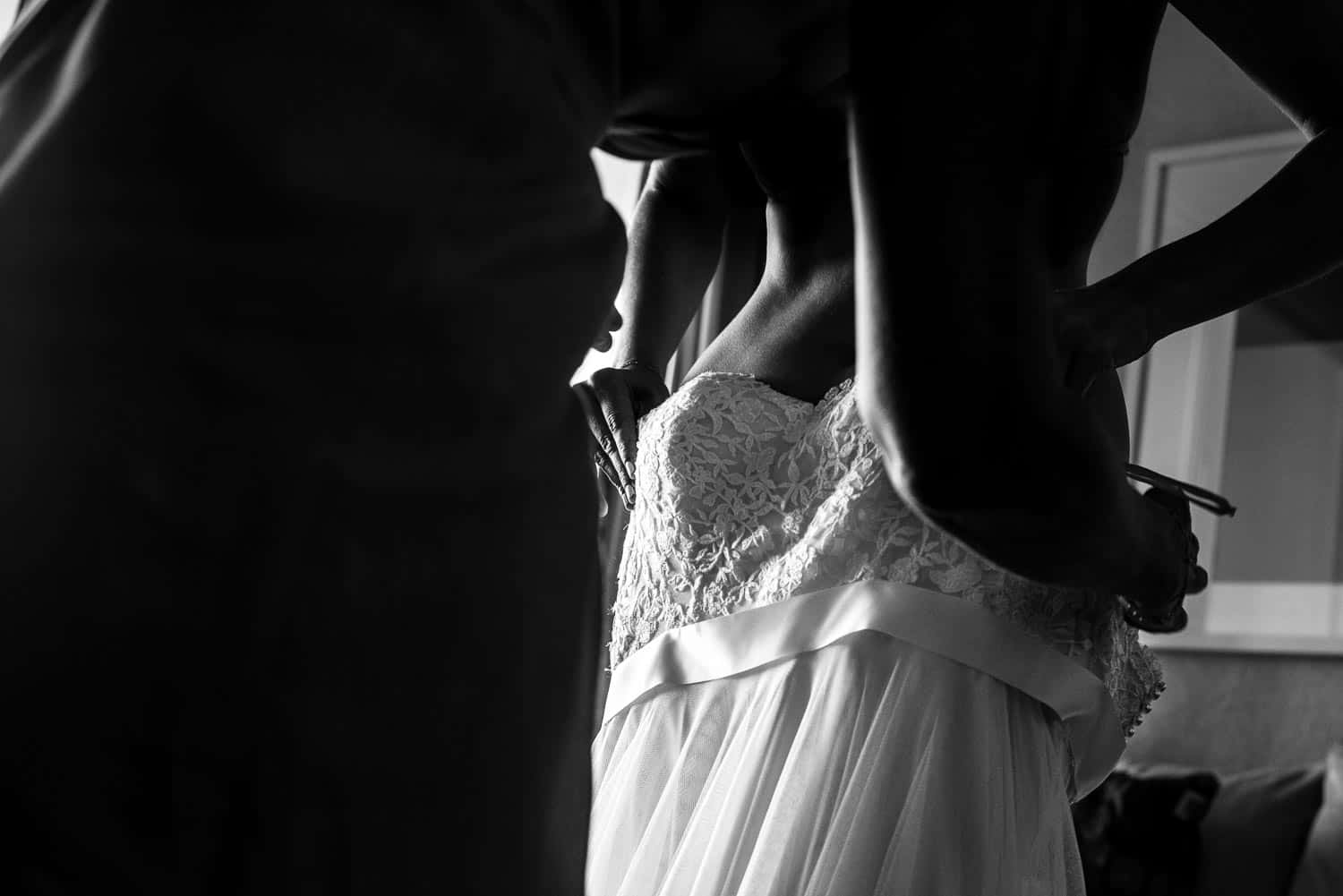 Sexy close up photo of bride putting on her dress
