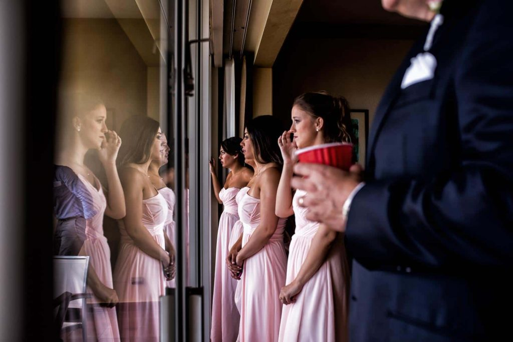 A group of bridesmaids looks out the window