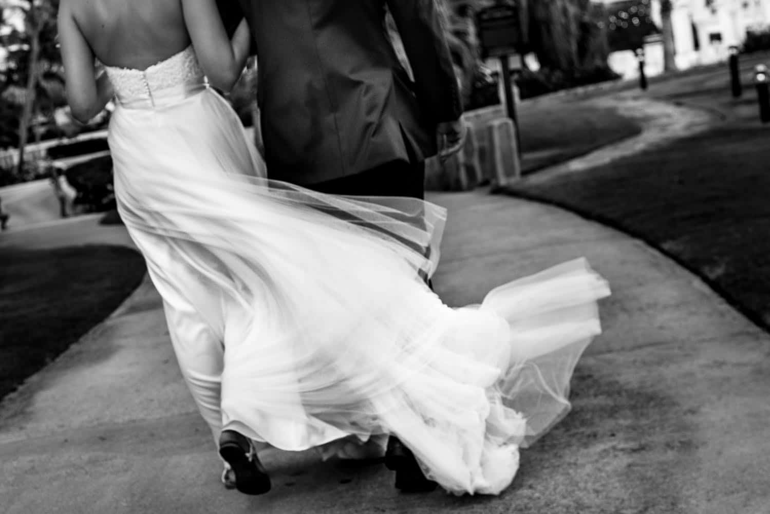 Black and white photo of a bride walking in windy weather with a flowing dress