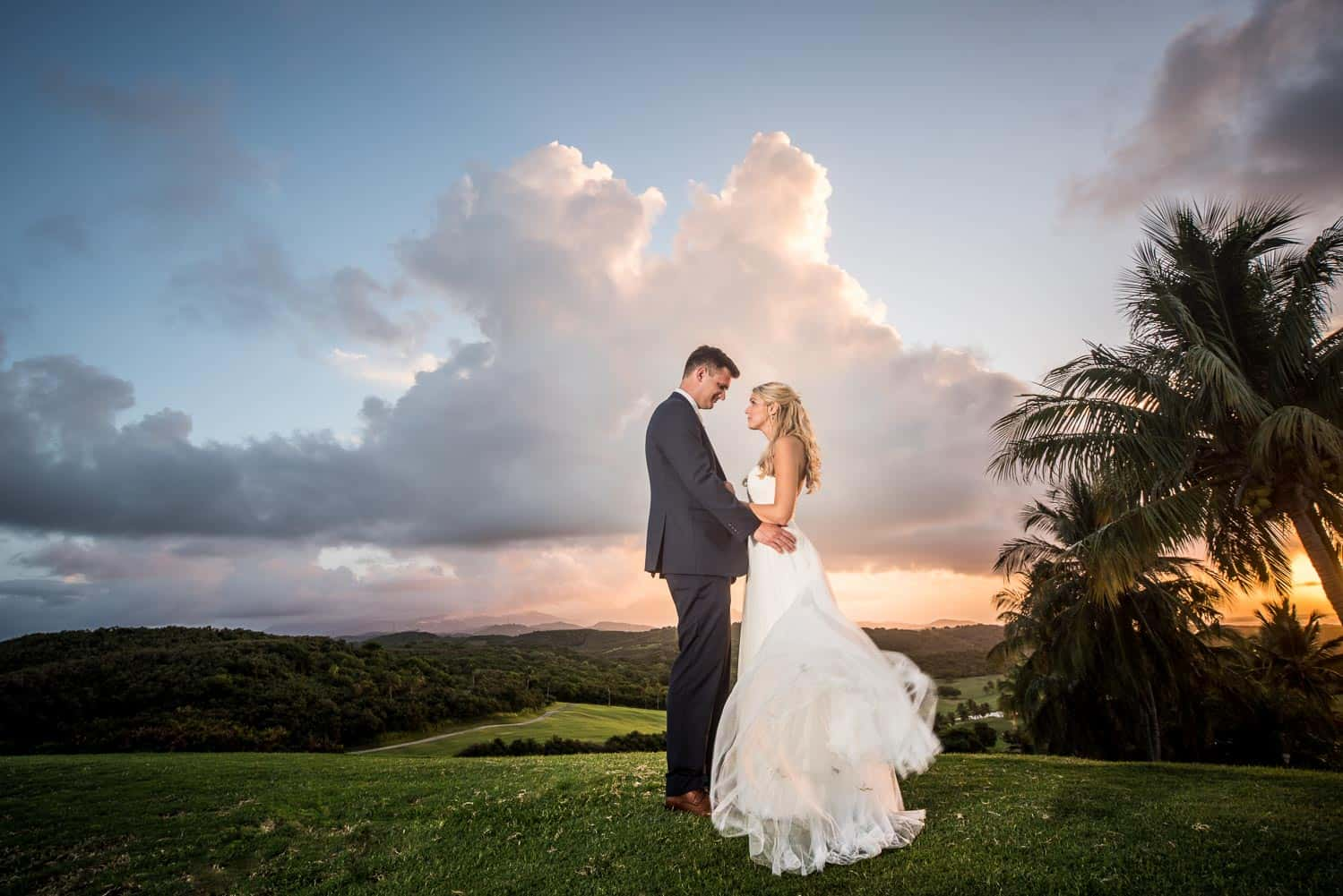 Bride and groom at El Conquistador Puerto Rico standing in front of a beautiful sunset
