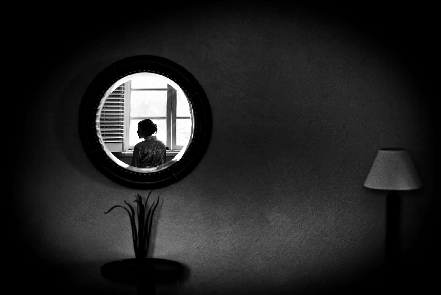 BW photo of a bridesmaid in a round mirror